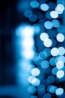 Éblouissement de bokeh de veilleuses de guirlandes bleues classiques de 2020 avec une lumière blanche au centre. fond vertical pour la créativité et le design.