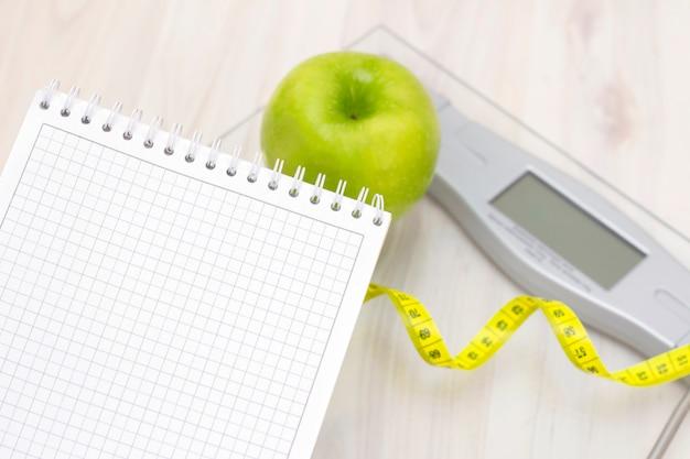 Des écailles, une pomme verte, un ruban à mesurer et un cahier pour écrire sur une surface en bois clair. préparation pour la saison estivale et la plage, perte de poids et concept sportif