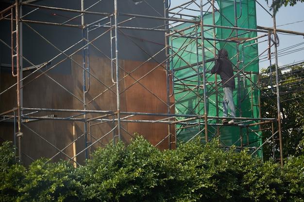 Un échafaudage de chantier avec un ouvrier non identifié fonctionne.jpg