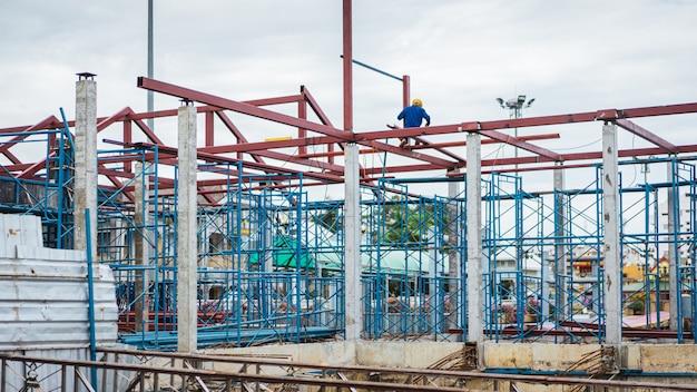 Échafaudage de maison, rénovation avec des ouvriers du bâtiment flou sur un échafaudage et du matériel au sol,