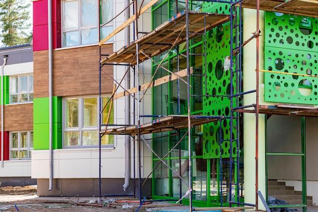 Échafaudage avec ponts en bois. réalisation de travaux de construction en hauteur. revêtement de la façade ventilée avec du métal.