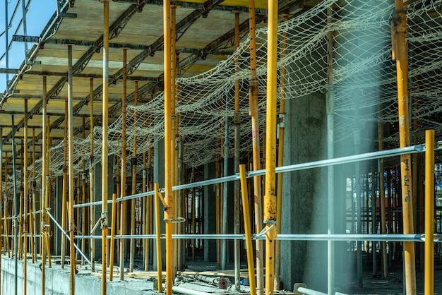 Échafaudage soutenant le coffrage de piliers en béton de certains bâtiments en construction.