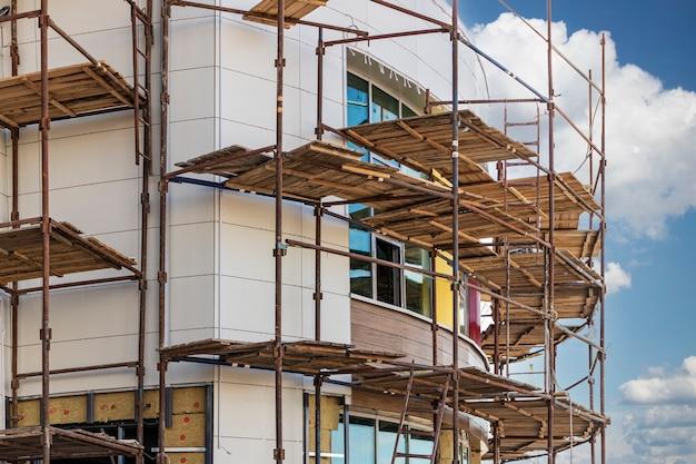 Échafaudages et échafaudages avec tabliers en bois, lors de la reconstruction du bâtiment. réalisation de travaux de construction en hauteur. sécurité des chantiers.