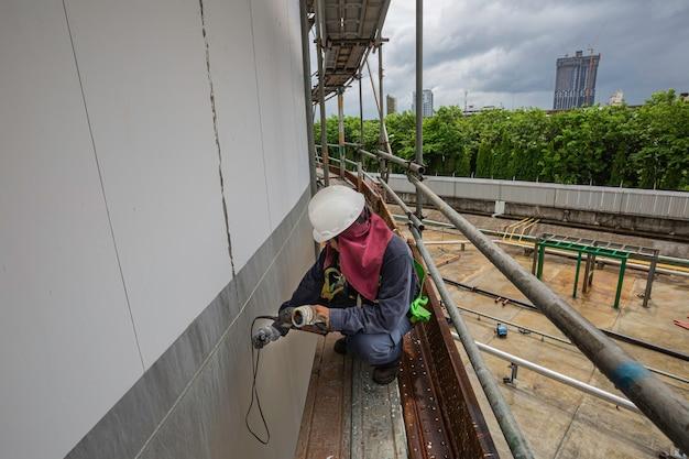 Les échafaudages de travailleurs masculins sont destinés à l'inspection de la plaque de coque d'épaisseur à ultrasons de l'huile de réservoir de stockage