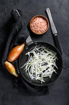 Échalote tranchée dans une poêle, cuisson des oignons frits. vue de dessus
