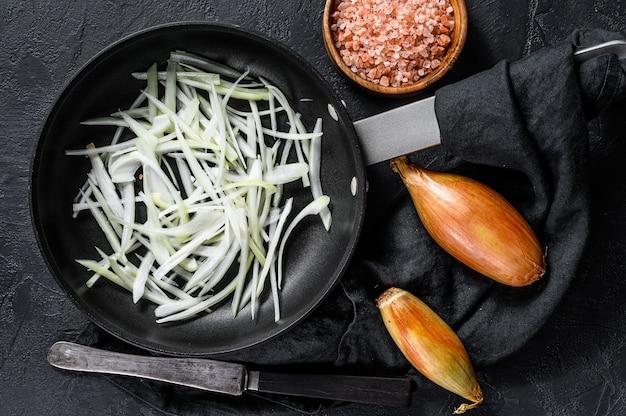 Échalote tranchée dans une poêle, cuisson des oignons frits.