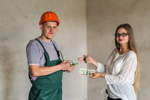 Échange entre constructeur homme avec clés et femme avec argent