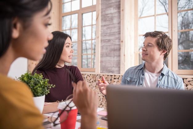 Échange d'idées. beaux jeunes collègues positifs assis à la table et se parlant tout en échangeant leurs idées