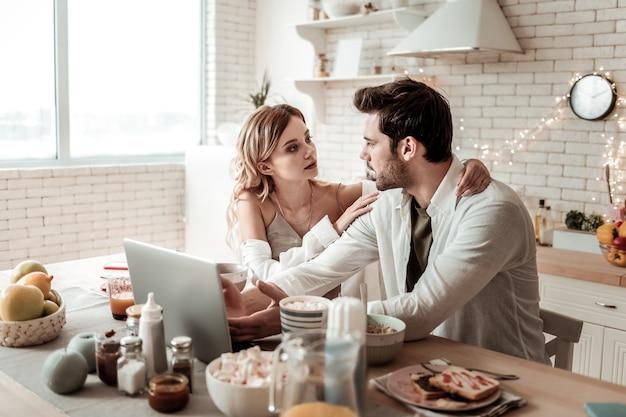Échange de pensées. jeune homme séduisant aux cheveux noirs dans une chemise blanche à la recherche de sérieux tout en regardant sa femme