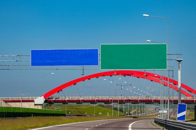 Échangeur d'autoroute avec pont et soleil en arrière-plan.