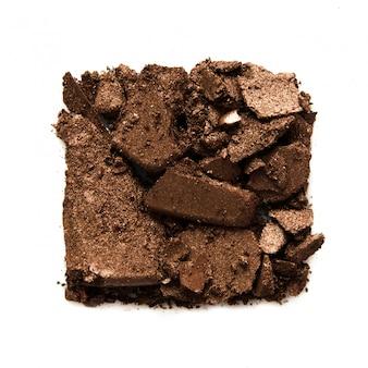 Échantillon de fard à paupières isolé. fard à paupières métallique brun écrasé. le concept de l'industrie de la mode et de la beauté.