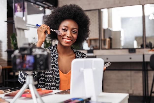 Échantillon. femme à la peau foncée positive avec des cheveux bouclés souriant brillamment tout en démontrant une nouvelle nuance de fard à joues