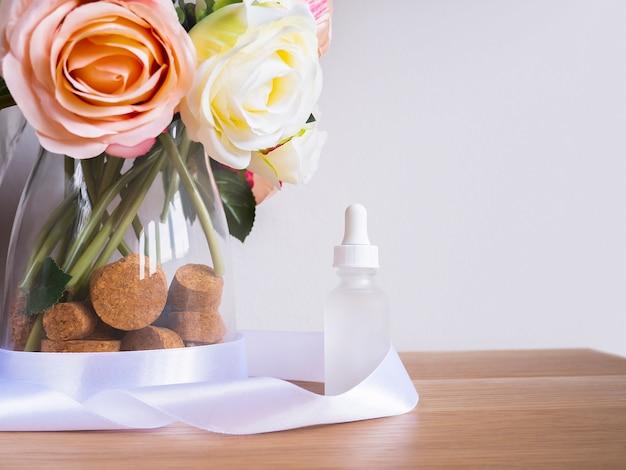 Échantillon d'huile de sérum de soin de la peau avec des roses sur la lumière