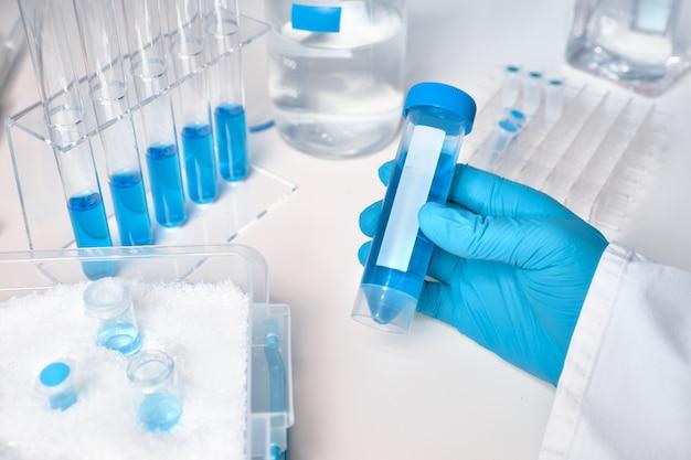 Échantillon liquide dans une main féminine gantée, échantillons de liquide bleu dans des tubes en verre et en plastique