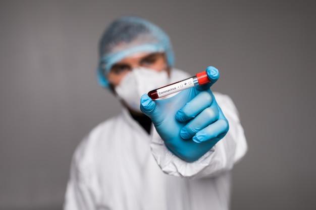 Échantillon de sang de coronavirus 2019-ncov. éclosion du virus corona. syndrome respiratoire à virus épidémique. homme en vêtements de protection tenant un test sanguin.