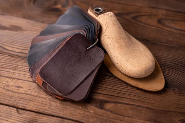 Des échantillons de cuir pour chaussures et chaussure en plastique durent sur une table en bois sombre