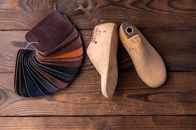 Des échantillons de cuir pour chaussures et chaussures en bois durent sur une table en bois foncé