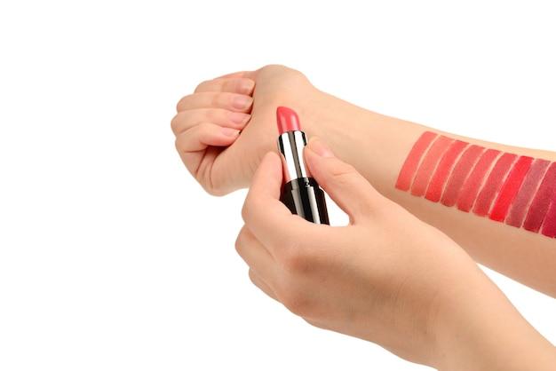 Échantillons de rouge à lèvres sur une main de femme isolée sur une surface blanche