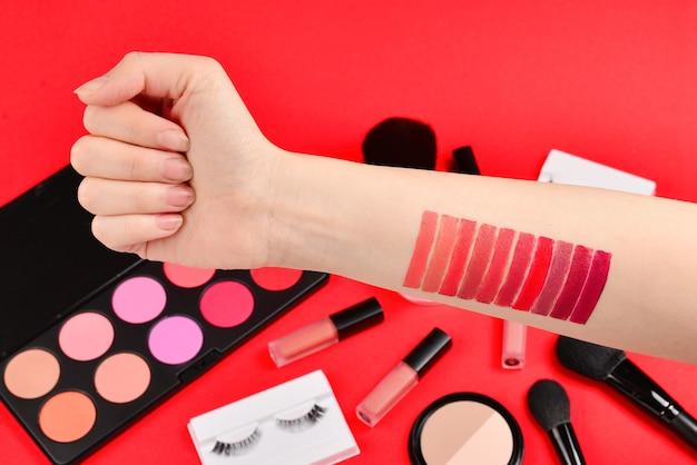 Échantillons de rouge à lèvres sur la main de la femme. produits de maquillage professionnels avec produits de beauté cosmétiques, fond de teint, rouge à lèvres, ombres à paupières, cils, pinceaux et outils.