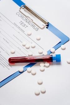 Échantillons de sang en gros plan avec des pilules et un formulaire médical