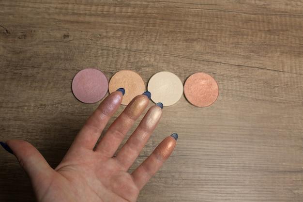 Échantillons de surligneur sur une main féminine sur un fond de bois en gros plan