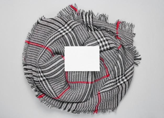 Écharpe femme à la mode avec une feuille de papier blanche au milieu pour l'espace de copie. temps de l'automne. vue de dessus