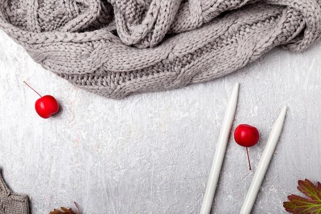 Écharpe grise, gants de chapeau près des aiguilles à tricoter sur gris. vue de dessus. copyspace. mise à plat