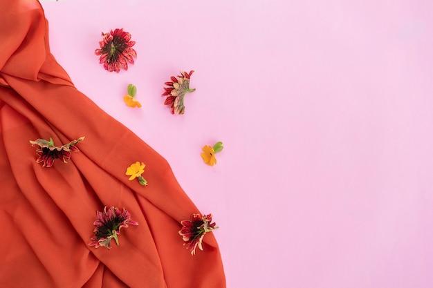 Écharpe orange, feuilles rouges et fleurs jaunes isolées sur fond rose, idée de concept minimale.