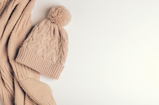 Echarpe en tricot un tuyau ou un collier de fils chauds et un bonnet beige avec un pompon.