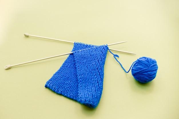 Écharpe tricotée avec des aiguilles à tricoter, fond vert jaune.