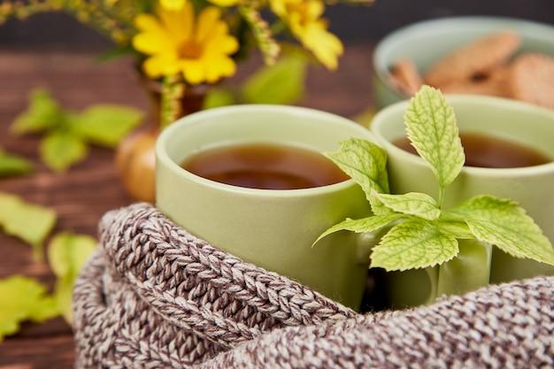 Écharpe tricotée avec une tasse de thé chaude.
