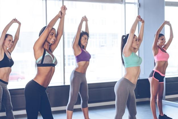 Échauffement. jeunes belles femmes gaies avec des corps parfaits en tenue de sport faisant des étirements avec le sourire tout en se tenant devant la fenêtre au gymnase