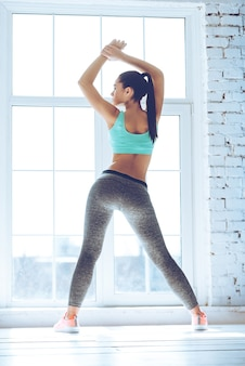Échauffement. vue arrière de la belle jeune femme en vêtements de sport faisant des étirements en se tenant debout devant la fenêtre de la salle de sport