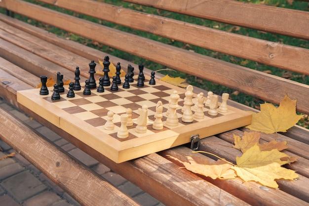 Échecs en bois sur le banc dans un parc de la ville. faible profondeur de champ. concentrez-vous sur les pièces blanches.