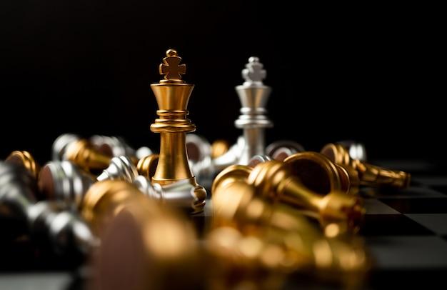 Les échecs du roi d'or et d'argent sont le dernier debout sur l'échiquier, concept de leadership commercial réussi, confrontation et perte