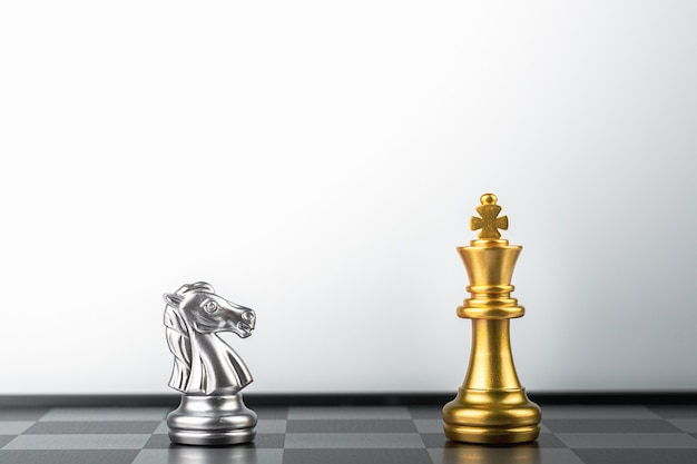 Les échecs du roi d'or debout rencontrent des ennemis chevaliers d'argent.