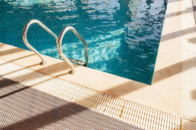 Échelle de barres d'appui dans la piscine bleue
