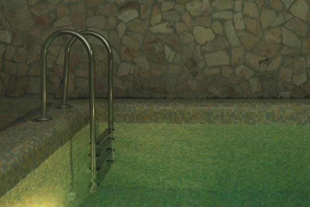 Échelle des barres d'appui dans la piscine verte