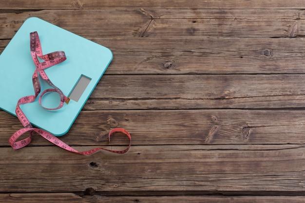 Échelle bleue et ruban rose sur une surface en bois sombre