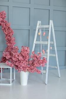 Échelle en bois et guirlande d'oeufs. échelle décorative et vase avec sakura à l'intérieur de la maison