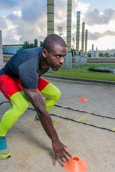 Échelle d'entraînement musculaire masculine au sol et aux cônes.