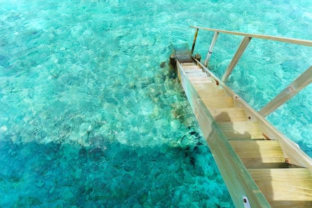 Échelle à la mer turquoise cristalline dans l'île tropicale des maldives