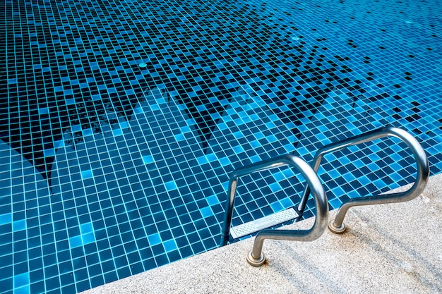 Échelle métallique en acier inoxydable dans la piscine bleue d'été