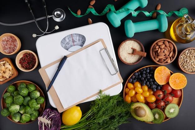 Échelle de perte de poids avec centimètre, stéthoscope, haltère, presse-papiers, stylo. concept de régime.