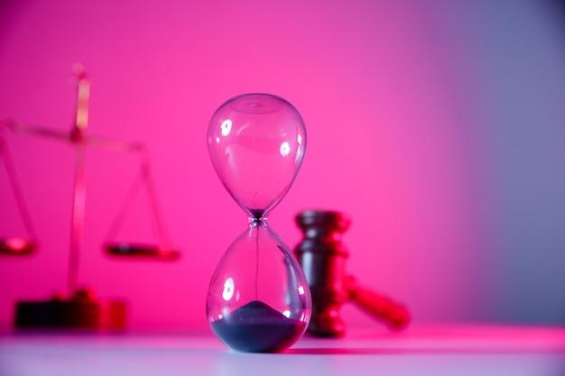 Échelles de sablier concept droit et justice et marteau de juge en bois en gros plan néon rose