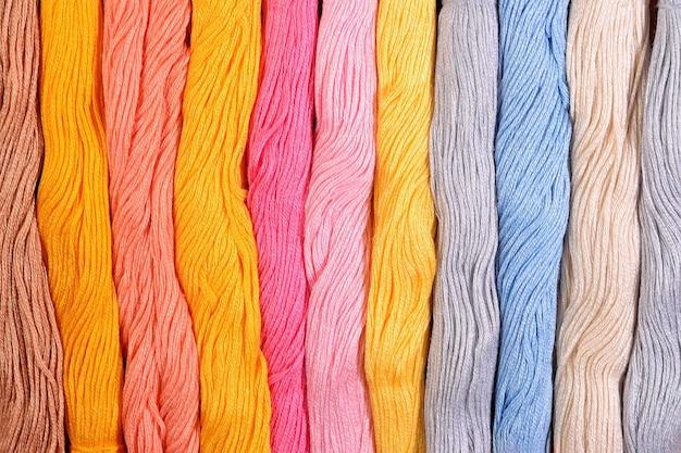 Écheveaux colorés de fil dentaire comme texture de fond se bouchent