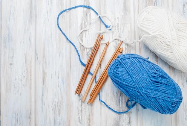 Écheveaux de fil et crochets pour tricoter sur une table en bois.