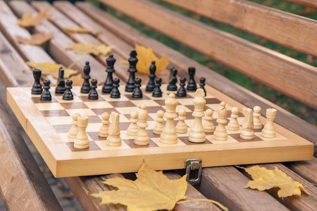 Échiquier en bois avec des pièces sur le banc dans un parc de la ville d'automne. faible profondeur de champ. concentrez-vous sur les pièces blanches.
