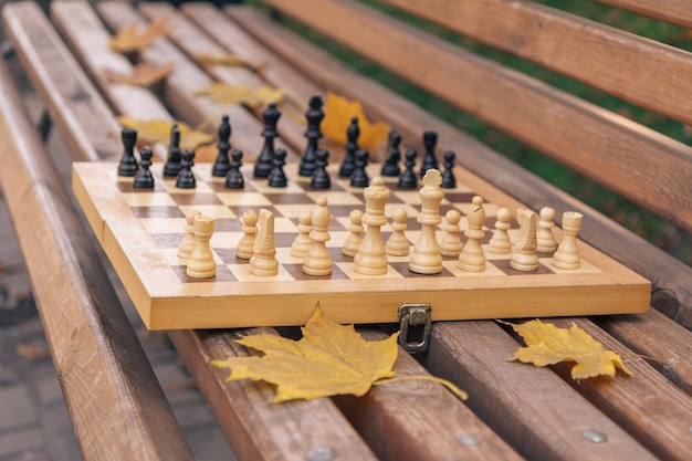 Échiquier en bois avec des pièces sur un banc dans le parc de la ville d'automne. faible profondeur de champ. concentrez-vous sur les pièces blanches.