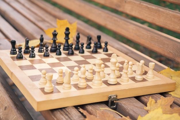 Échiquier en bois avec des pièces sur le banc dans un parc de la ville. faible profondeur de champ. concentrez-vous sur les pièces blanches.